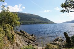 Sjö för landskapod-blått och blå himmel med moln i skotsk Skotska högländerna Royaltyfria Bilder