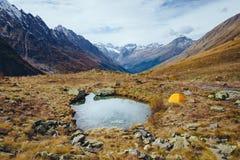 Sjö i bergen i nedgången och det gula tältet fotografering för bildbyråer