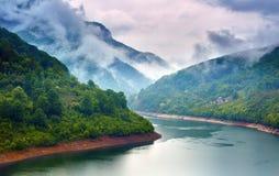 Sjö i bergen på en dimmig dag Arkivfoton