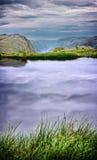 Sjö i bergen, sjö och himmel i bergen, fjord i Norge, reflexionen av himlen, vattnet, gräset på sjön Arkivbilder