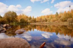 Sjö i höstfärger Vaggar blå himmel avstånd royaltyfria bilder