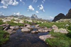 Sjö i Pirineos berg med moln och himlar i himlen, Spanien arkivbilder