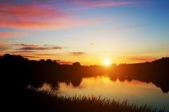 Sjö i skog på solnedgången romantisk sky Arkivfoto