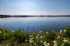 Sjö med blått vatten och blommor på förgrund Fotografering för Bildbyråer