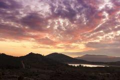 Sjö mellan berg i den fantastiska solnedgången Royaltyfri Foto