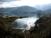 Sjö och berg och liten by, härligt landskap Arkivfoto