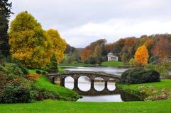 Sjö och bro i höst - Stourhead trädgård Royaltyfri Foto