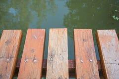 Sjö och flödande flod med en träbro Arkivfoton
