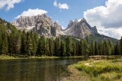 Sjö och liten träbro framme av berg Royaltyfria Bilder