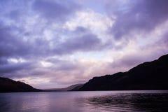 Sjö på solnedgången med purpurfärgad himmel Arkivfoto