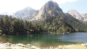 Sjö som omges av skogar och berg i Pyrenees arkivbilder