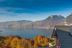 SJÖ THUN, SCHWEIZ - OKTOBER 27, 2015: Höstsikt av sjön Thun och den typiska Schweiz byn nära stad av Interlaken Royaltyfria Foton