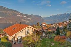 SJÖ THUN, SCHWEIZ - OKTOBER 27, 2015: Höstsikt av sjön Thun och den typiska Schweiz byn nära stad av Interlaken Arkivfoto
