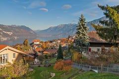 SJÖ THUN, SCHWEIZ - OKTOBER 27, 2015: Höstsikt av sjön Thun och den typiska Schweiz byn nära stad av Interlaken Royaltyfria Bilder