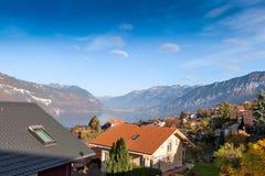 SJÖ THUN, SCHWEIZ - OKTOBER 27, 2015: Höstsikt av sjön Thun och den typiska Schweiz byn nära stad av Interlaken Fotografering för Bildbyråer