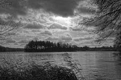 Sjö under den dramatiska molnig himmel och vassen i en förgrund för bw-framsida för bakgrund svart le för foto Royaltyfria Bilder