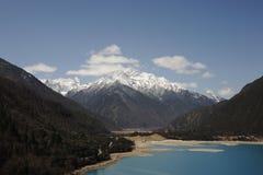 Sjö vid snöberg i Tibet Arkivfoto