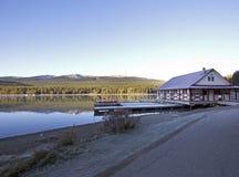 Sjöbod med röda kanoter på sjön Arkivbild