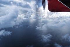 Sjöflygplanflyg till och med molnen över havet för Maldive ö Arkivfoton