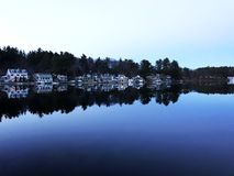 Sjöhus på en fortfarande blå sjö Royaltyfri Bild