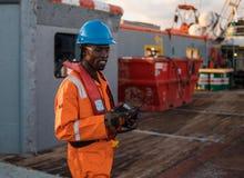Sjöman AB eller Bosun på däck av den frånlands- skytteln eller skeppet, bärande PPE Arkivbild
