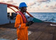 Sjöman AB eller Bosun på däck av skytteln eller skeppet, bärande PPE Arkivfoto