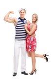 Sjöman som böjer hans bicep och poserar med flickvännen Arkivbilder