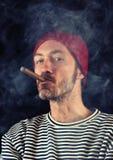 Sjöman som röker en cigarr Fotografering för Bildbyråer