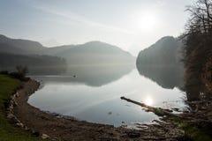 Sjön Alpsee på en dimmig dag med solen som kommer till och med nära Royaltyfri Bild