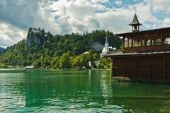 Sjön blödde med slotten på en kulle i en bakgrund, slovenian fjällängar Royaltyfri Bild