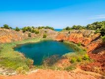 Sjön i gamla röda jorder för bauxit` ett s bryter sten grottan i Apulia, Otranto, Salento, Italien arkivfoton