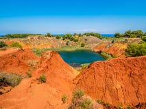 Sjön i gamla röda jorder för bauxit` ett s bryter sten grottan i Apulia, Otranto, Salento, Italien arkivbild