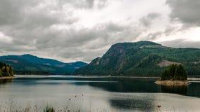 Sjöplats med berg och en ö arkivfoton