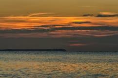 Sjösida i Lohme med solnedgången och Kap Arkona på bakgrunden, Tyskland arkivbild