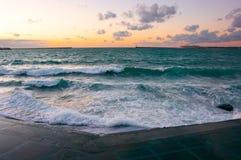 Sjösida mot havet med bränning på solnedgången arkivbilder