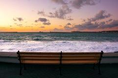 Sjösida mot havet med bränning på solnedgången royaltyfri bild