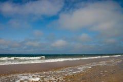 Sjösida på dagtid med blå himmel och moln Royaltyfri Fotografi