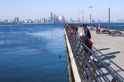 Sjösidan parkerar, Baku, Azerbajdzjan - April 17, 2017 En grupp av sportfiskare fiskar i Kaspiska havet från pir Arkivfoto