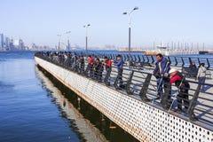 Sjösidan parkerar, Baku, Azerbajdzjan - April 17, 2017 En grupp av sportfiskare fiskar i Kaspiska havet från pir Royaltyfri Fotografi