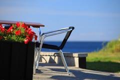 Sjösidatabell och stolar framme av huset Fotografering för Bildbyråer