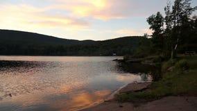 Sjösolnedgång med berg stock video