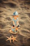 Sjöstjärna med diagramet av en pojke på sanden Arkivbild