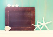 Sjöstjärna och skal med en svart tavla Arkivfoto