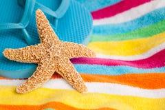 Sjöstjärnan och flipen plumsar på en strandhandduk Royaltyfria Bilder