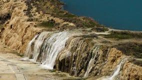 Sjövatten som applåderar över kant för travertinesjöhandfat lager videofilmer