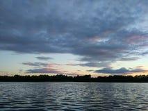 Sjöyttersida på aftonen i Lettland, Östeuropa Landskap med vatten och skogen royaltyfria bilder