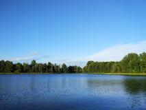 Sjöyttersida på aftonen i Lettland, Östeuropa Landskap med vatten och skogen royaltyfri bild