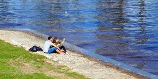 sj?lv Förälskelse-, teknologi-, förhållande-, familj- och folkbegrepp - ungt par för lyckligt leende, vid floden St Petersburg royaltyfri fotografi