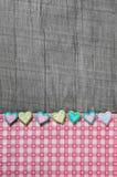 Sjaskig chic grå träbakgrund med hjärtor på en rosa vit c Arkivfoto