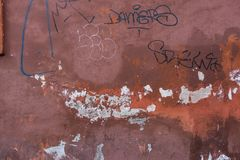 Sjaskig gammal röd betongvägg med attraktioner arkivbild